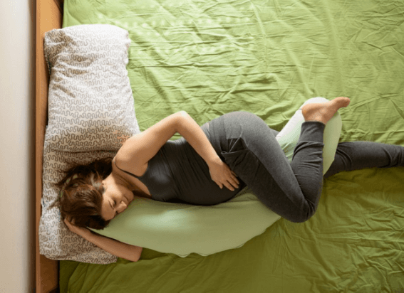 A pregnant woman lying on her side with a pregnancy pillow.